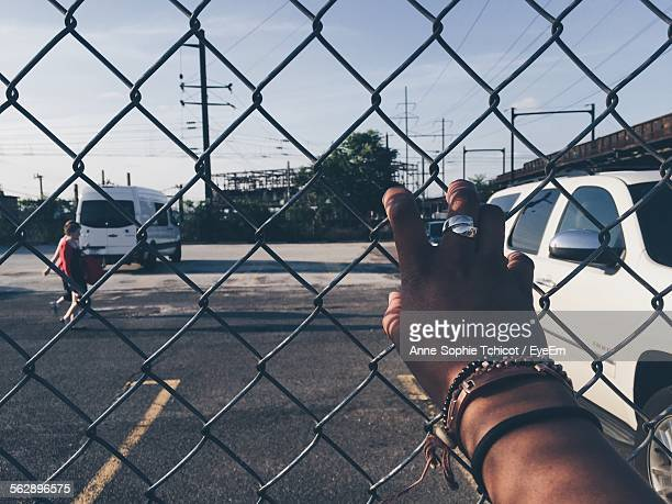 Cropped Hand On Chainlink Fence Against Parked Car On Street
