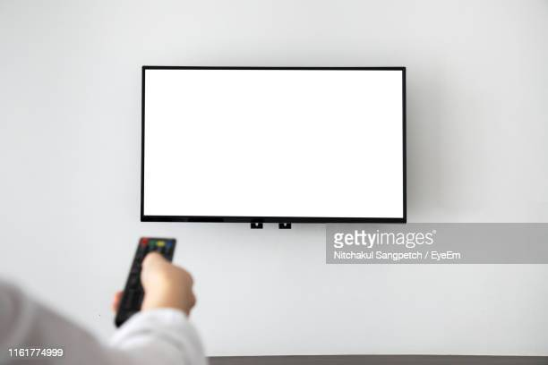 cropped hand operating television with remote control - televisor - fotografias e filmes do acervo