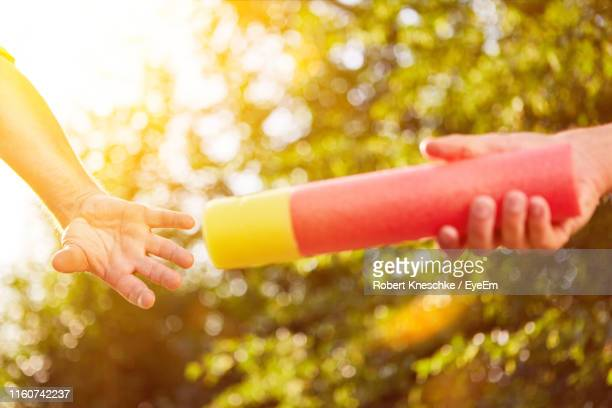 cropped hand passing relay baton to friend against trees - passing sport stock-fotos und bilder