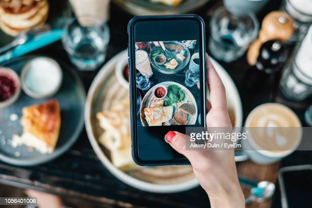 cropped hand photographing food with smart phone - 写真を撮る ストックフォトと画像