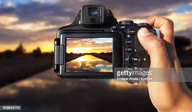 cropped hand photographing lake against sky during sunset - digital camera stock pictures, royalty-free photos & images
