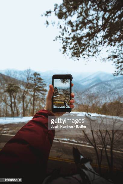 cropped hand photographing landscape during winter - hamiltonmusical stockfoto's en -beelden