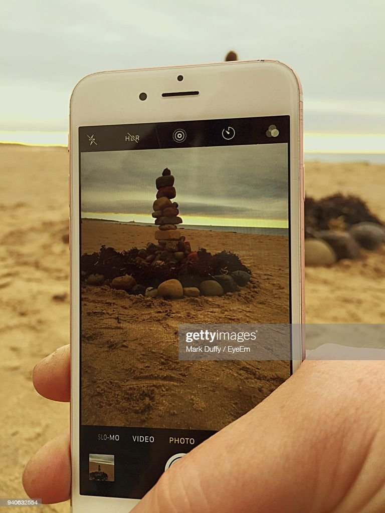 Cropped Hand Photographing Stacked Stones From Mobile Phone At Beach : Stock Photo