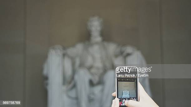 Cropped Hand Photographing Statue Of Abraham Lincoln From Smart Phone