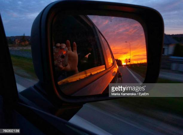 Cropped Hand Photographing Sunset Reflection Of Side-View Mirror