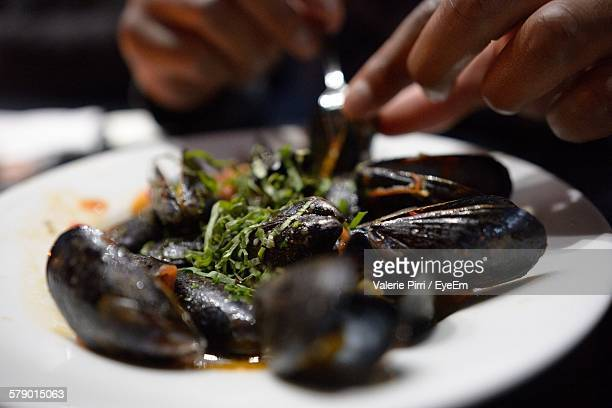 Cropped Hand Picking Mussels On Plate At Restaurant