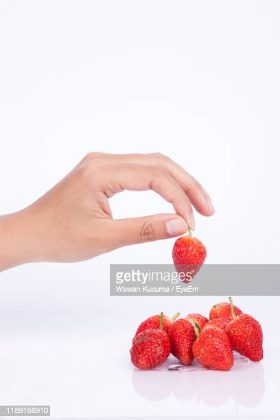 cropped hand picking strawberry against white background - 狩りをする ストックフォトと画像