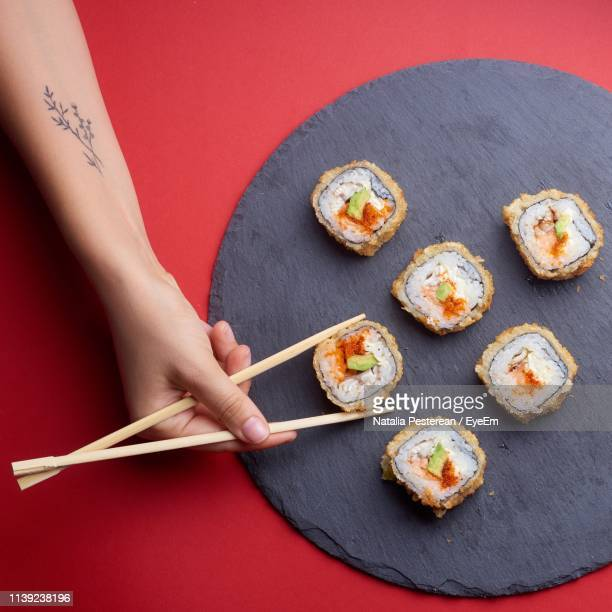 cropped hand picking sushi from plate on table - sushi stock pictures, royalty-free photos & images