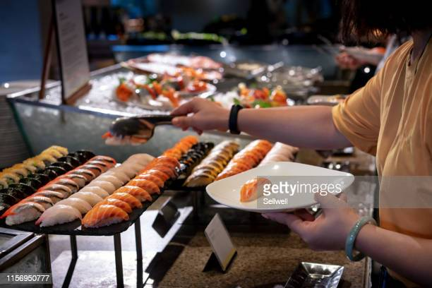 cropped hand picking sushi on the table - raw food diet stock pictures, royalty-free photos & images