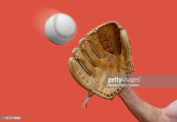 cropped hand playing baseball against red background - baseball glove stock pictures, royalty-free photos & images