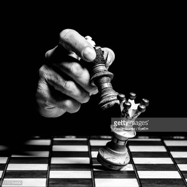 cropped hand playing chess in darkroom - chess stock pictures, royalty-free photos & images