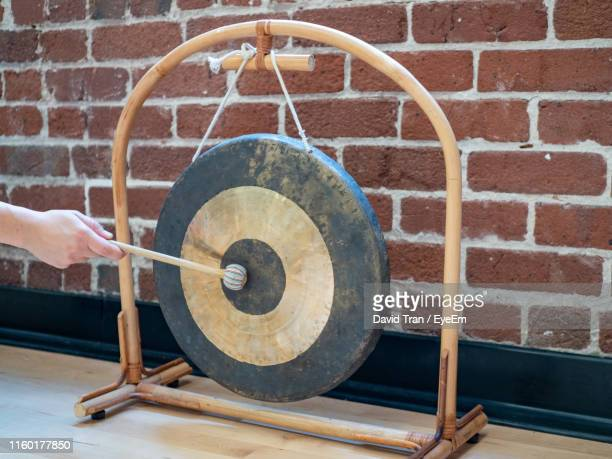 cropped hand playing gong against brick wall - gong stock photos and pictures