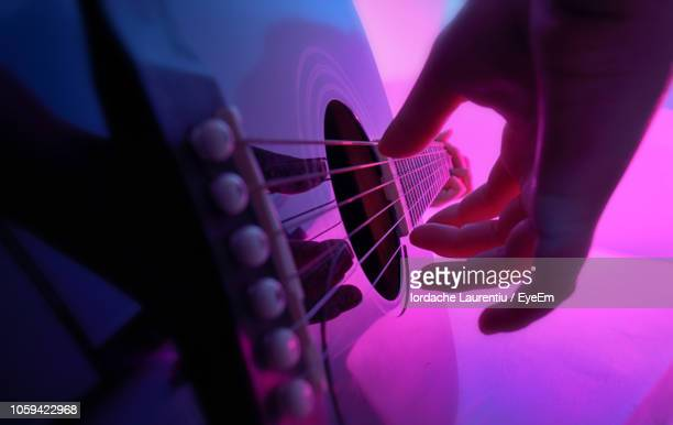 cropped hand playing guitar - acoustic guitar stock pictures, royalty-free photos & images
