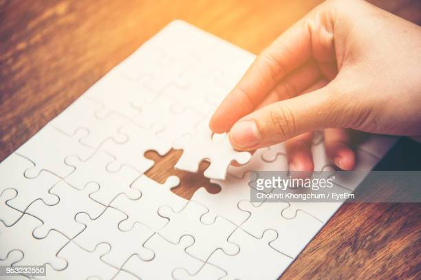 cropped hand playing jigsaw puzzle on wooden table - jigsaw piece stock pictures, royalty-free photos & images