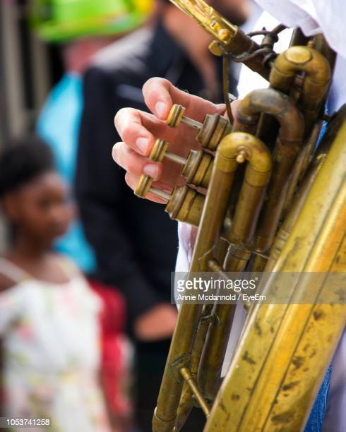 cropped hand playing trumpet - annie musical stock photos and pictures