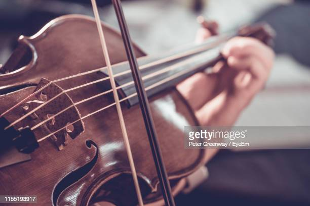 cropped hand playing violin - bicester village stock pictures, royalty-free photos & images