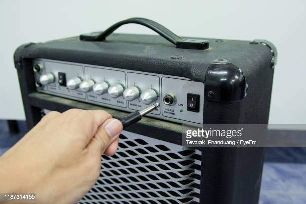 cropped hand plugging audio cable in amplifier - plugging in stock pictures, royalty-free photos & images