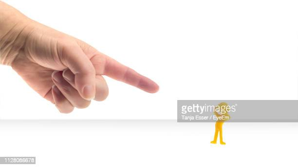 cropped hand pointing at yellow figurine over white background - scolding stock photos and pictures