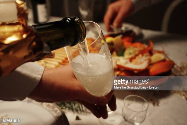 Cropped Hand Pouring Champagne In Flute From Bottle Over Table