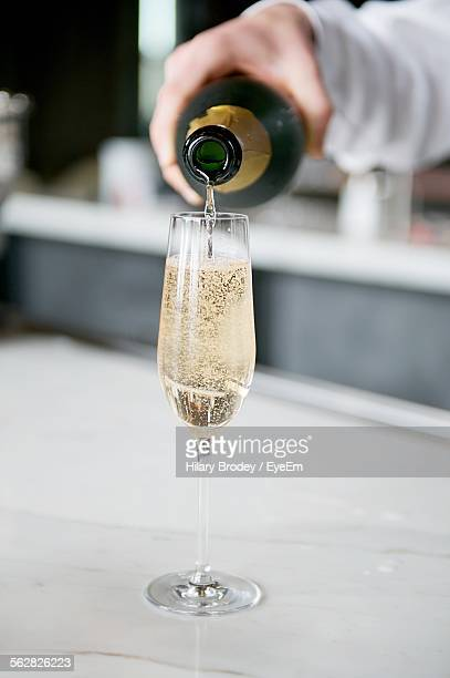 Cropped Hand Pouring Champagne In Glass