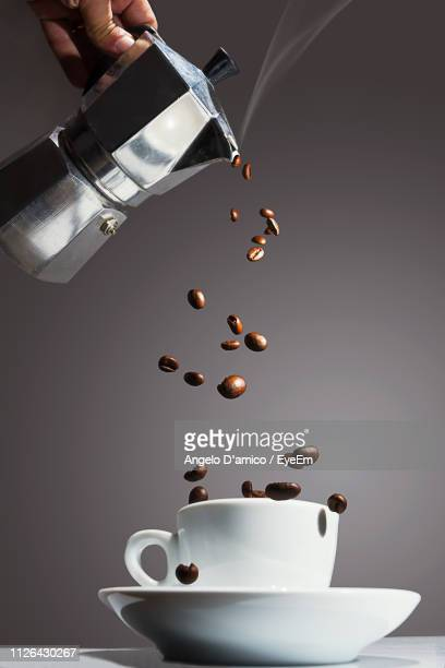 Cropped Hand Pouring Coffee Beans In Cup On Table