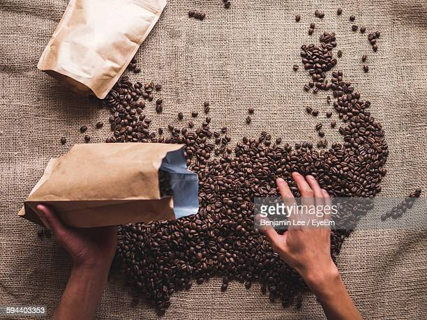 Cropped Hand Pouring Coffee Beans In Package