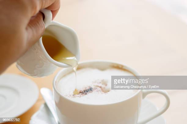 Cropped Hand Pouring Drink In Coffee