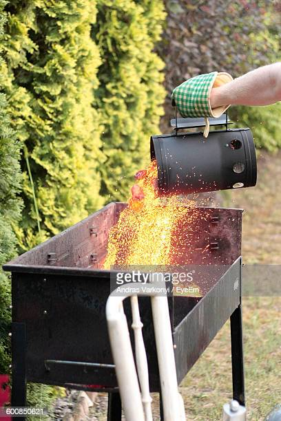 Cropped Hand Pouring Hot Charcoal In Barbecue