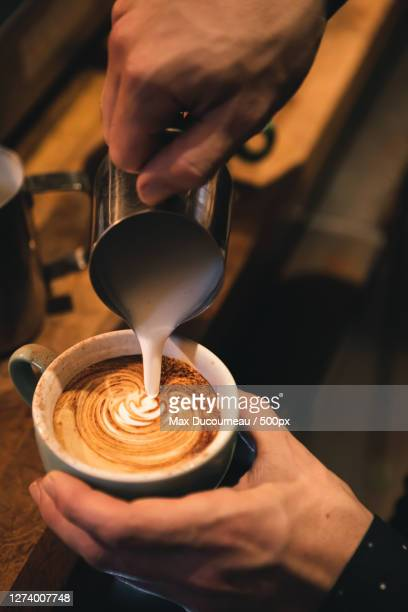 cropped hand pouring milk in coffee cup, london, united kingdom - preparation stock pictures, royalty-free photos & images