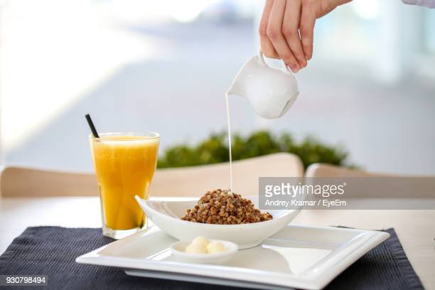 Cropped Hand Pouring Milk On Food By Drink At Restaurant