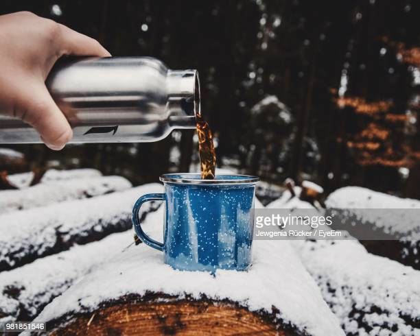 cropped hand pouring tea in cup on snow covered log - warme dranken stockfoto's en -beelden
