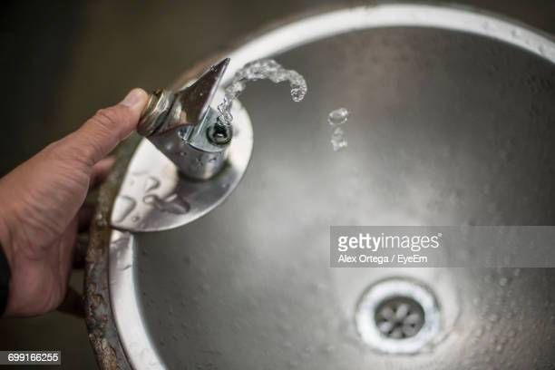 Cropped Hand Pressing Faucet Button Of Drinking Fountain