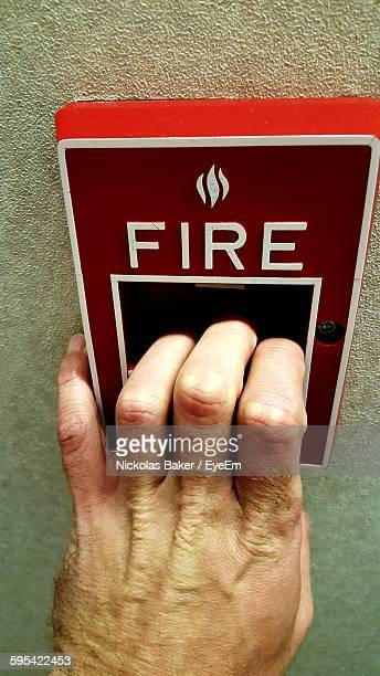 Cropped Hand Pulling Down Fire Alarm On Wall