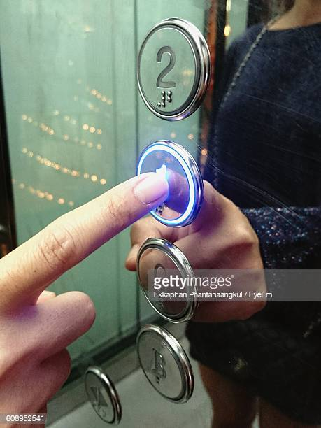 Cropped Hand Pushing Elevators Button