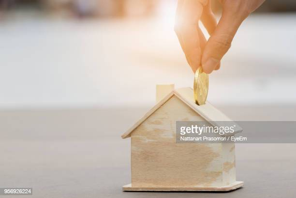 cropped hand putting gold coin in house shaped piggy bank on table - sparbüchse stock-fotos und bilder