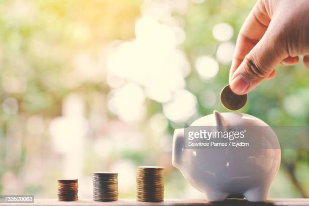 Cropped Hand Putting Money Into Piggy Bank By Coins Stack On Table