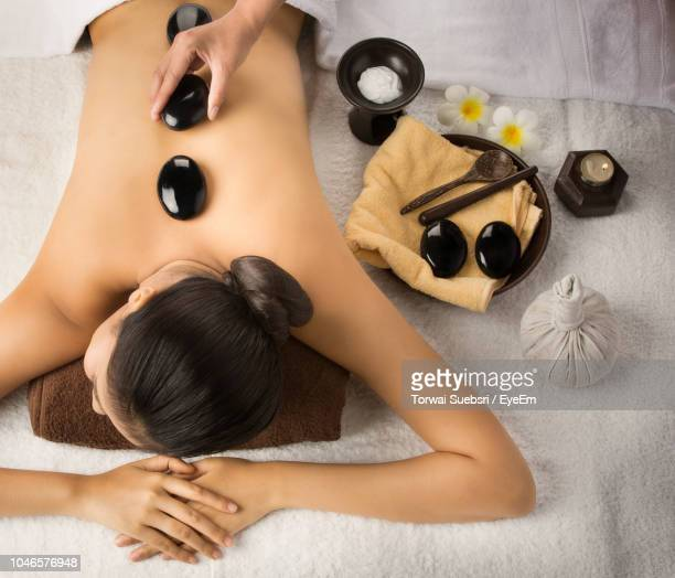 cropped hand putting stones on woman back at spa - torwai stock pictures, royalty-free photos & images