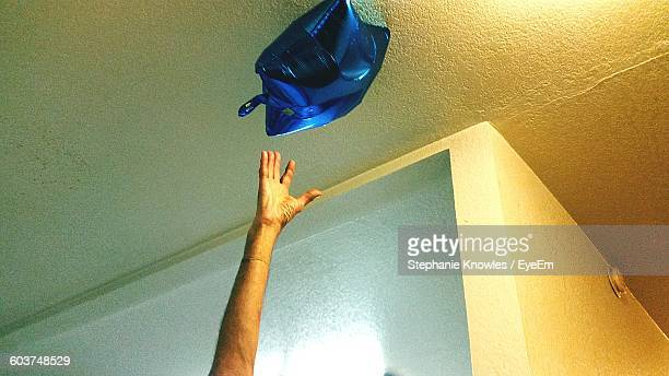 Cropped Hand Reaching Blue Star Balloon At Home