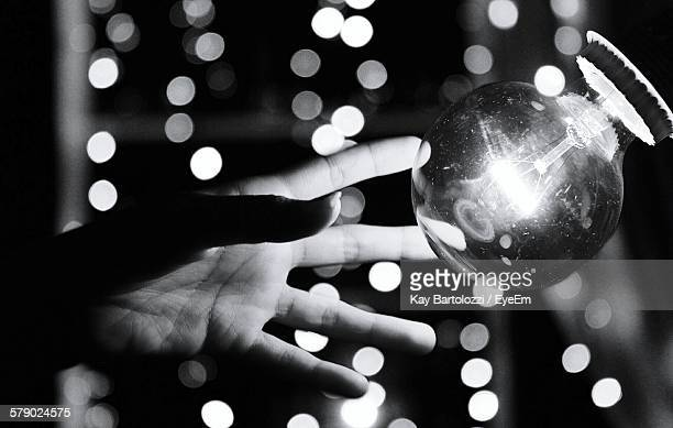 Cropped Hand Reaching For Light Bulb