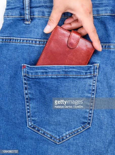 cropped hand removing wallet from back pocket of jeans - pantalón fotografías e imágenes de stock