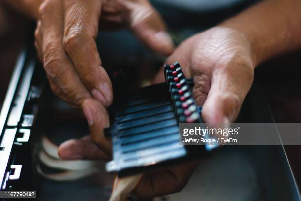 cropped hand repairing technology - jeffrey roque stock photos and pictures