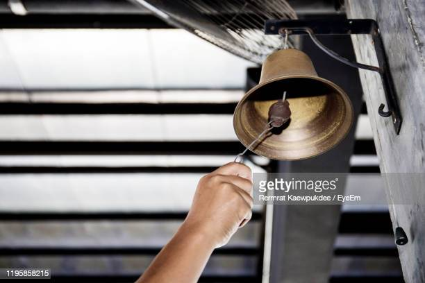 cropped hand ringing bell on wall - bell stock pictures, royalty-free photos & images