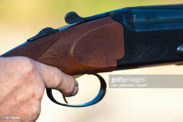 cropped hand shooting gun - trigger stock photos and pictures