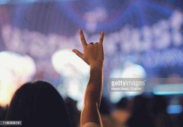 cropped hand showing horn sign against blurred background - popular music concert stock pictures, royalty-free photos & images