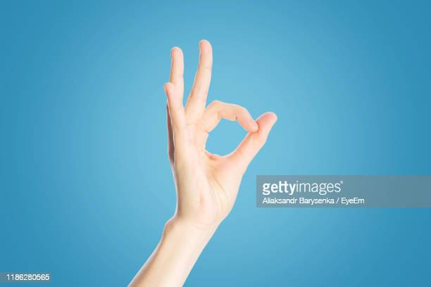 cropped hand showing ok sign against blue background - ok sign stock pictures, royalty-free photos & images