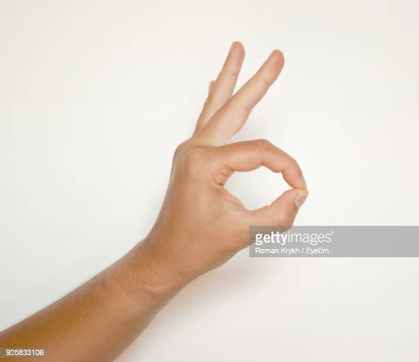 Cropped Hand Showing Ok Sign Against White Background