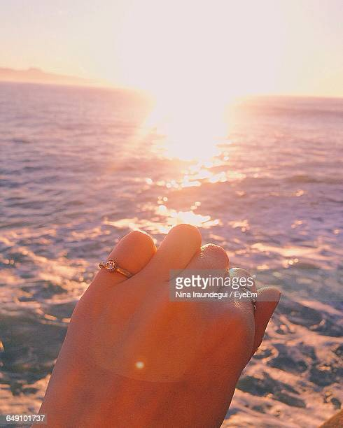 Cropped Hand Showing Rings Against Sea During Sunset