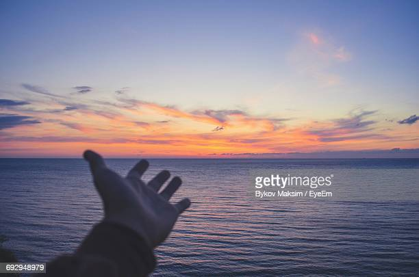 Cropped Hand Showing Sea At Sunrise