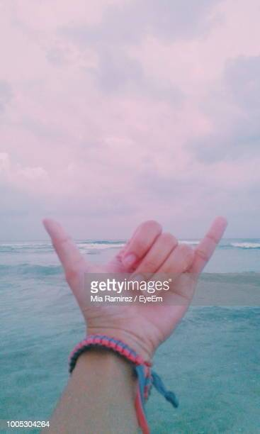 Cropped Hand Showing Shaka Sign At Beach