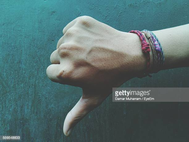cropped hand showing thumbs down sign - dismissal stock photos and pictures